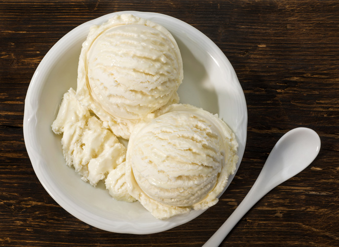 Vanilla ice cream in a bowl with a spoon on a wooden board